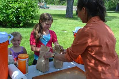 Sisters Melody Langan and Eme Loucks picked up two free sack lunches—turkey/spinach wraps, string cheese, carrots and broccoli with ranch dip, and orange slices—at the Twisp park last Thursday. Photo by Laurelle Walsh