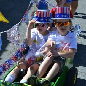 Garrett, left, and Gavin Maxwell get into the spirit of the Fourth of July in a parade float driven by their grandfather Gary Maxwell, and designed by Gene Westlund. Twelve grandkids in total rode the Maxwell/Westlund family float. Photo by Laurelle Walsh