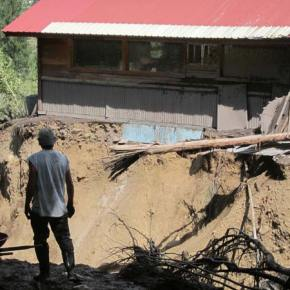 Bob Elk looks at his shop, separated from his home by a gorge cut by the mudslide. Photo by Don Nelson