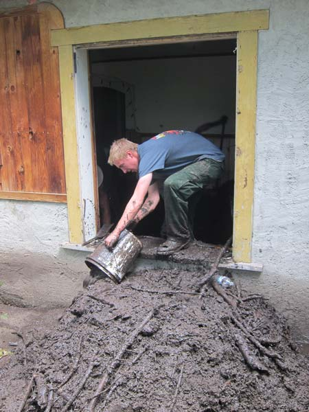 Dumping mud out of a side window of the Elk/Lewis home. Photo by Don Nelson