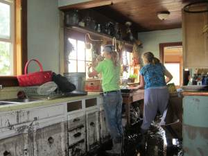 Janie Lewis, right, salvages what she can from her kitchen. Photo by Don Nelson
