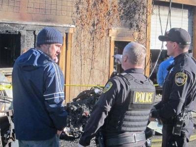 Photo by Don NelsonTwisp River Pub owner Aaron Studen, left, Twisp Police Chief Paul Budrow and Okanogan County Sheriff's Deputy Ottis Buzzard discussed the damage caused by a fire at the pub early Monday morning.