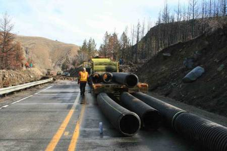 Photos by Marcy StamperWSDOT crews set up piping for a temporary culvert that will replace the one clogged by the mudslide.