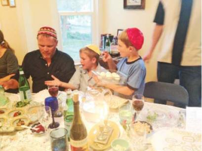 Photo courtesy of Sarah Schrock Greg and Keller Knaub, and Quin Smith, eat hard-boiled eggs as part of a Seder dinner at the Cortes home on Burgar Street.