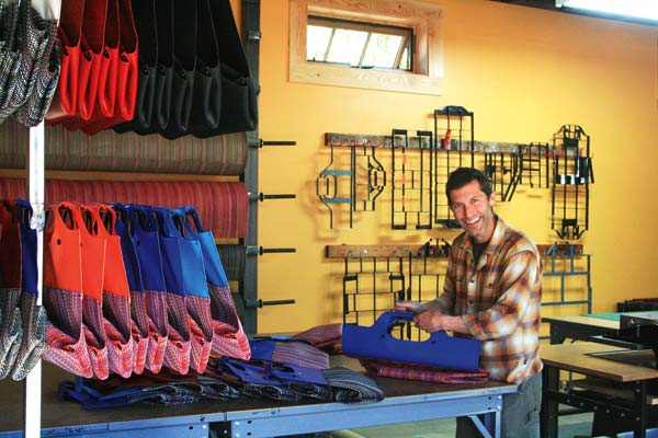Photo by Marcy Stamper Jonathan Baker, founder and senior designer of eqpd, trimmed bags in the company's new, expanded production space.