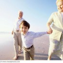 Close-up of a boy holding his grandparents hands on the beach