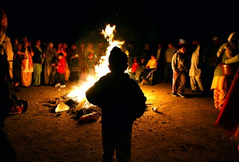 Members of the Sikh Gurdwara Guru Angad Darbar Temple gather around a bonfire as they observe the Lohri Festival, a popular harvest celebration, in Bakersfield, 2009. Members toss rice and peanuts into the fire offering up prayers and best wishes for family members and friends. - The Bakersfield Californian