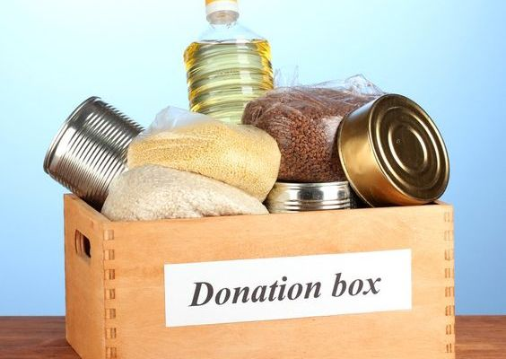 Donation box with food on blue background close-up