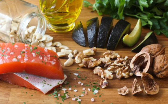 Salmon seasoned with salt, cashews, walnuts, sliced avocado, and olive oil on a butcher block, garnished with parsley.