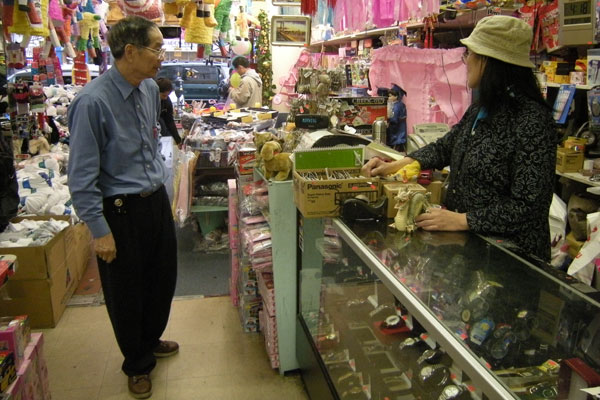 FEW CUSTOMERS: Maisie Wong (right) talk to her boss, Chek Chew Ng as two customers take a look at goods in their store. Wong said her store sales continued to plunge, so she had no choices but to lay off workers. (Moch N. Kurniawan)