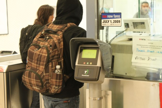 Muni patrons pass by the TransLink card reader at the Montgomery Street Station Tuesday night