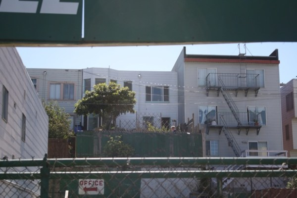 The view from Mission Street of Heidi working in her backyard.