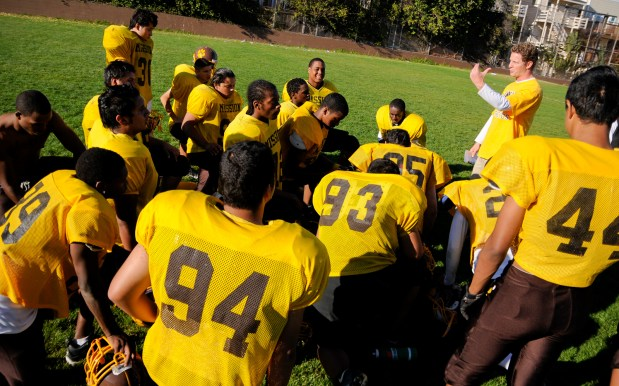 The Mission High School football team huddles around Coach Joe Albano after practice on Wednesday. The Bears face Lowell High School Thursday afternoon.