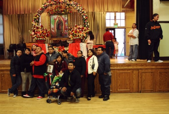 A family has their photo taken in front of one of the shrines, while the crew volunteers gets ready for the next mass, at noon.
