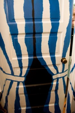 Brenda Kett, clothing designer, peers from her fanciful bathroom door on 19th Street, in one of several large and lovely apartments in the former synagogue. Brenda has lived here for 29 years.
