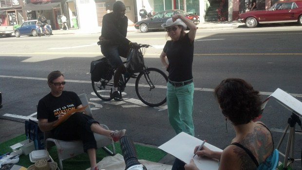 Sophia Green, a member of Mission Artists United, models in a pop-up parklet as people stop to sketch her.