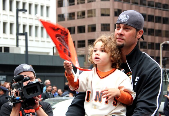 Giants pitcher Ryan Vogelsong holds his daughter as they ride along the parade route. Photo by Chelsi Moy.
