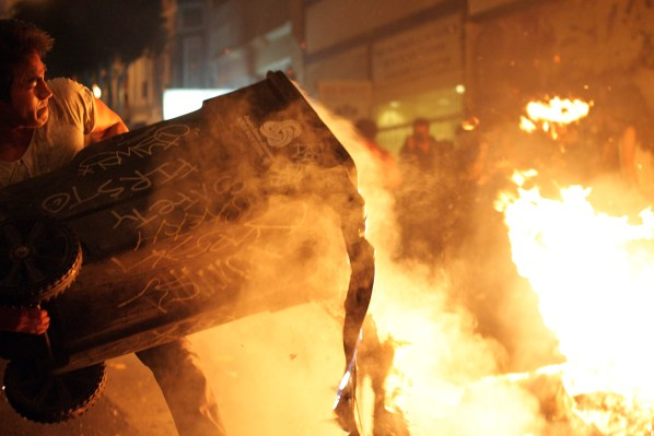 A fan throws a burning garbage can to a bonfire on 19th and Mission streets. Photo by Rigoberto Hernandez