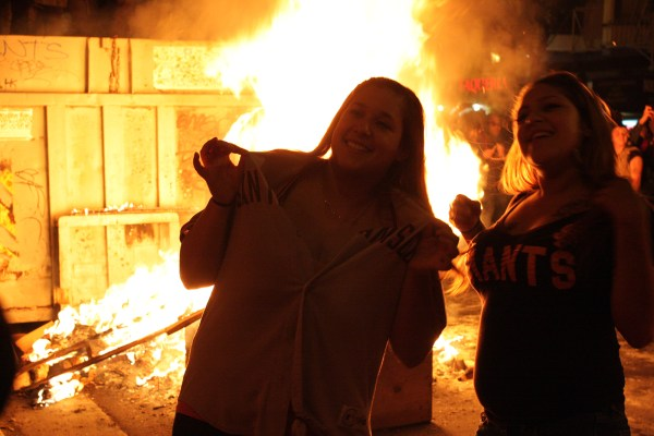 Giants fan pose for a photo in front of a bonfire on 22nd and Mission streets on Sunday. Photo by Rigoberto Hernandez