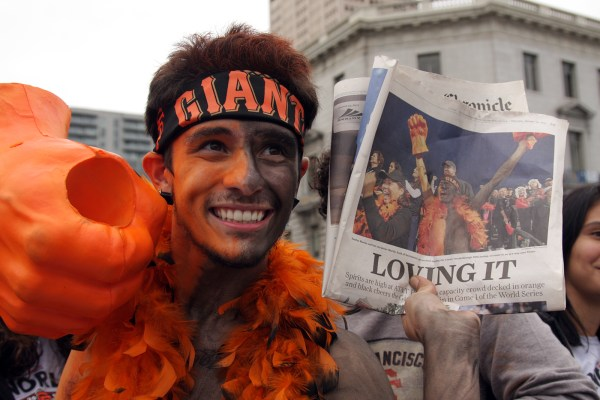 A Giants fan holds up a paper near City Hall. Photo by Rigoberto Hernandez.