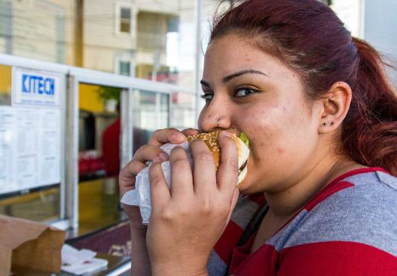 Melina Rosales bites into a big cheeseburger at the Whiz Burgers counter. She says she'd much rather eat at a local establishment like the Whiz than visit a chain burger place like McDonalds. She appreciates the vintage style of the Whiz, and, she says, the parking lot.
