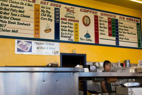 Whiz Burgers Drive-In has preserved the style of many relics from its past, including this long hand-painted sign that hands above the burger line in the kitchen.