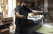 Image shows a man putting carbon fiber into a guitar mold.