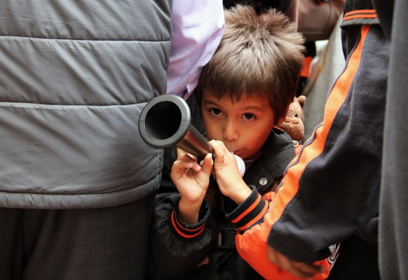 A little boy blows a horn as he waits for the parade to start. Photo by Jamie Goldberg.