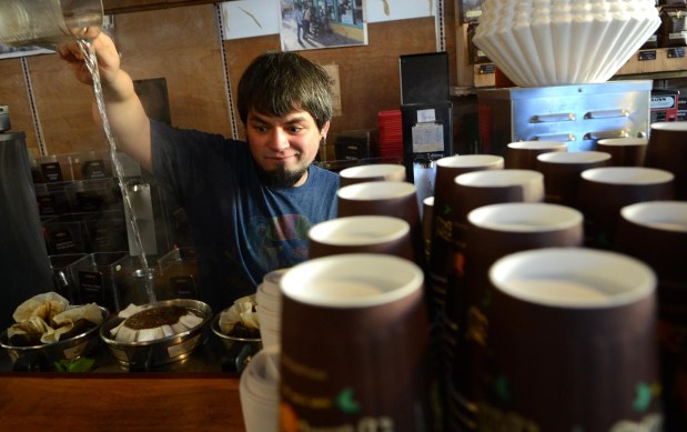 Tony Kincses, a barista at Philz Coffee on 24th Street, makes coffee for patrons.