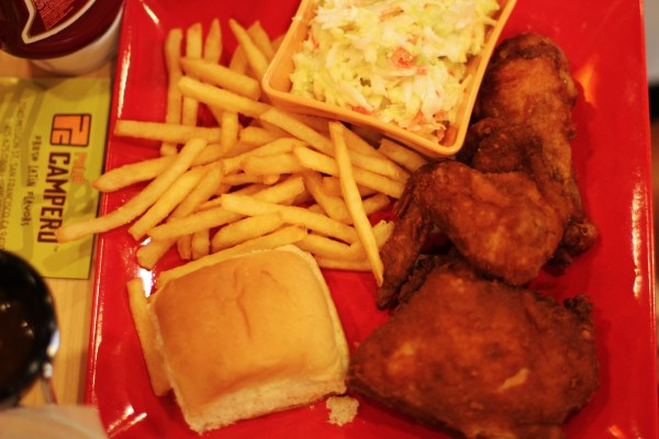 Chicken, bread, french fries, and salad on plates at Pollo Campero. Photo by Claudia Escobar.