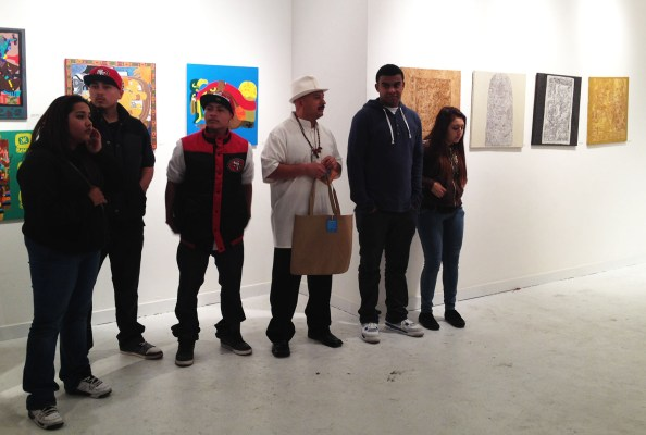 Hernandez and his students who have their art showcased behind them.