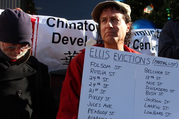Tommi Avicolli Mecca, director of the counseling program at the Housing Rights Committee of San Francisco, holds up a sign listing streets where tenants are being evicted under the Ellis Act.