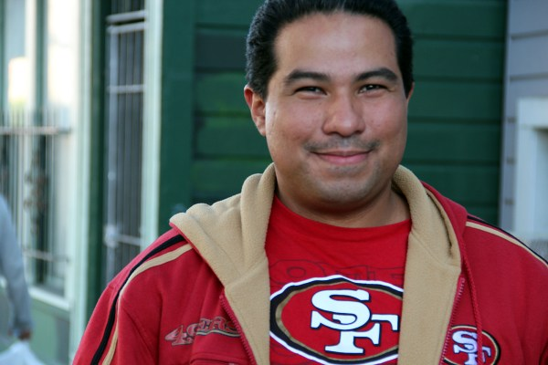 "Nelson Arias dons his 49ers gear as he walks on 23rd Street. Simply put, the 49ers will win ""because we're better,"" he says."