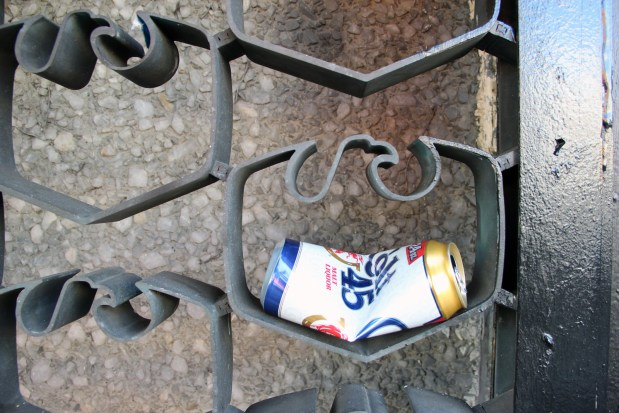 A beer can crushed to fit into the fences of the US Bank on the corner of Mission and 22nd.