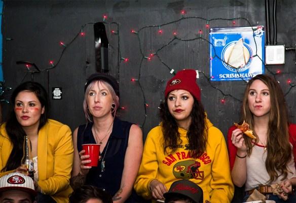 Cuatro muchachas viendo el juego en Gestalt, sobre la calle 16. Foto de Marta Franco.