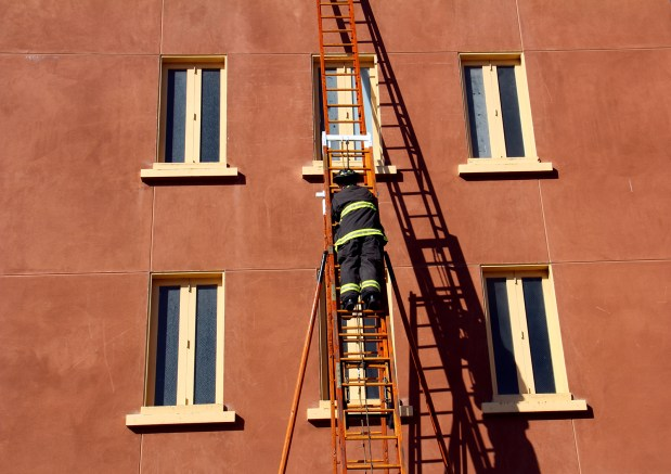 A firefighter works on a ladder drill at the Mission Fire Department. Photo by Molly Oleson