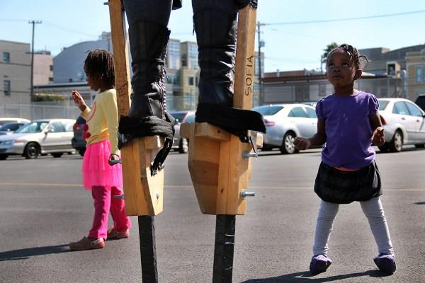 A child looks up at a stilt-walker.
