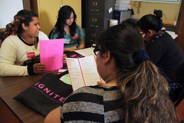 Young women engage in exercises and conversation during a workshop.