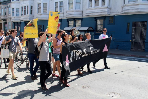 A group of people protesting San Francisco evictions marches down 18th Street.