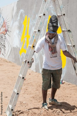 Festigraff day 1: Docta (Amadou Lamine Ngom), pioneer graffiti artist, President of Doxadem Squad and organizer of Festigraff, prepares to work on the upper reaches of his mural.