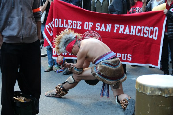 A dancer takes a bow at the end of the performance in front of the CCSF banner.