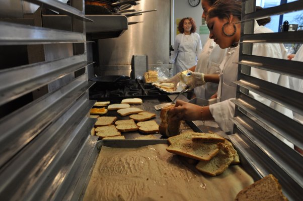 From back to front: Jasmine James, Yannery Nieto, and Sharon Rapalo preparing lunch in the kitchen.