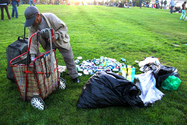 A man, who declined to give his name, sorts through garbage in Dolores Park on Sunday. Considering how many people visit the park, many park goers think that it is clean compared to other places.