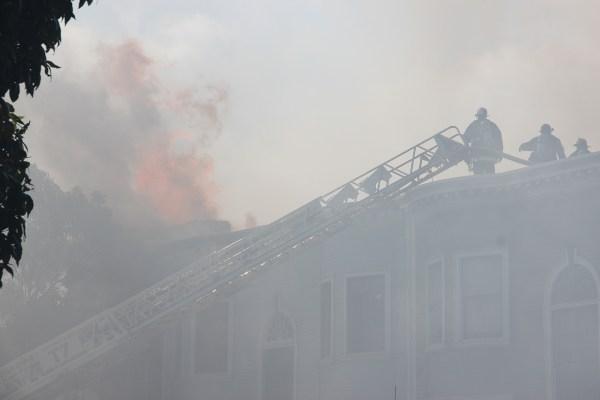 SFFD battles flames atop 1450 Valencia Street. By Greta Mart.