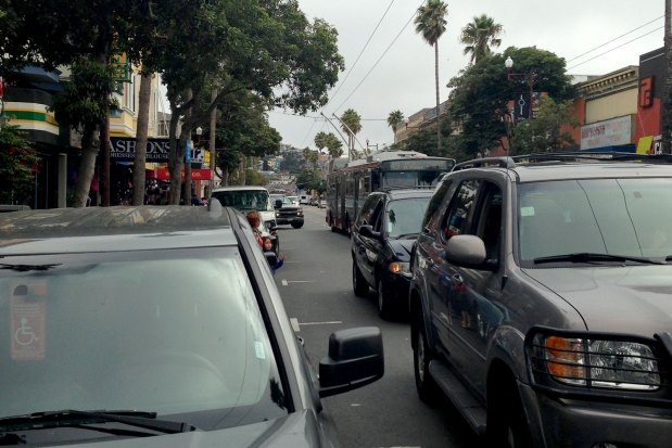 Two double-parked vehicles force a bus to change lanes on Mission Street.