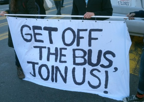 Portesters hold a sign in front of Apple bus at event on December 20. A bit more of a collaborative approach than in Oakland.