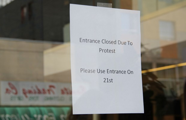 A sign on the door of Vanguard Property during the anti-eviction protest.