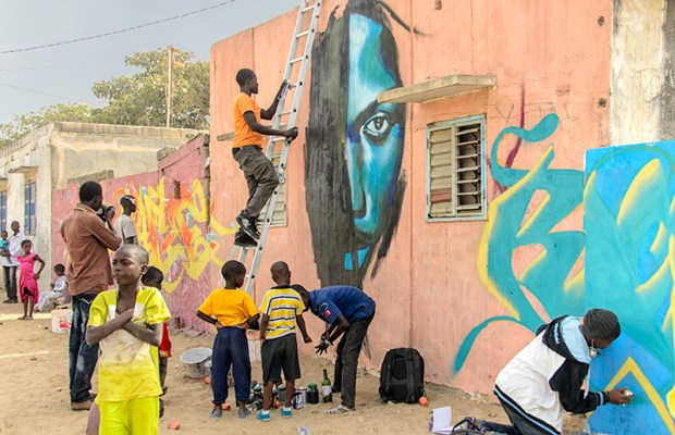 Wall #2: As the neighbors create an impromptu street party, graffeurs Chimère and Mbautta work on their murals.