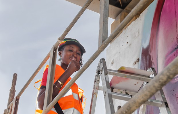 For the first time, several women participate in Festigraff. This apprentice artist gives the high sign from atop her scaffold on the Toll Highway.