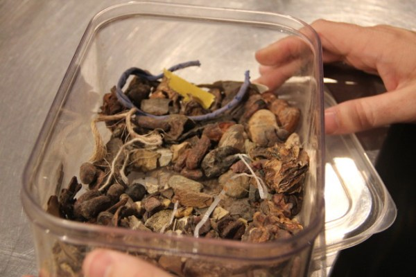 """The leftovers: Twine, bark, plastic, even small or cracked beans are removed into this box. """"People have been collecting their own piles,"""" an employee said. Photo by Joe Rivano Barros."""